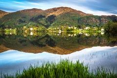 Berglandschaft mit einem ruhigen Dorf, einem grünen Wald und einer See-Reflexion im Sommer lizenzfreie stockbilder