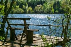Berglandschaft mit Holzbank nahe einem See Stockfotografie