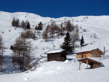 Berglandschaft mit Schnee und Holzhäusern Stockfotografie