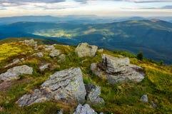 Berglandschaft mit Steinen im Gras auf Abhang und Blau Stockfotos