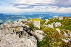 Berglandschaft mit Steinen im Gras auf Abhang und Blau Stockfotografie