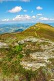 Berglandschaft mit Steinen im Gras auf Abhang und Blau Stockbilder