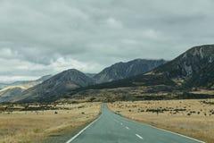 Berglandschaft mit Straße und blauem Himmel, Otago, Neuseeland Stockbilder