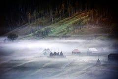Berglandschap met de mist van de de herfstochtend bij zonsopgang Royalty-vrije Stock Foto