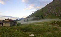 Berglandschap met een schuilplaatstoevluchtsoord vroeg in de ochtend Stock Foto's