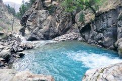 Berglandschap met een waterval en een snelle stroom van ijzig blauw bergwater stock foto's