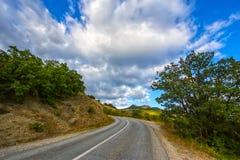 Berglandschap met het winden van weg Stock Foto's