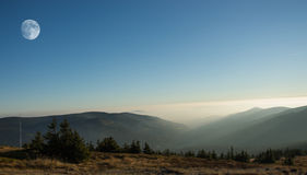 Berglandschap met moonrise Mistige dag Stock Fotografie