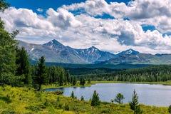 Berglandschap, witte wolken, meer en bergketen in de afstand Fantastische zonnige dag in bergen, groot panorama stock foto's