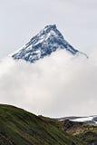 Berglandskap av Kamchatka: Kamen Volcano i moln Royaltyfri Bild