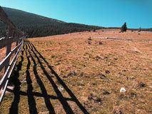 Berglandskap bredvid ett utsmyckat staket royaltyfria foton