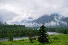 Berglandskap i dimman och molnen till floden Royaltyfri Foto