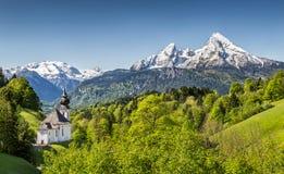 Berglandskap i fjällängarna med kyrkan, Bayern, Tyskland royaltyfri foto