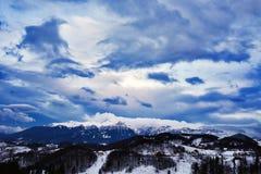 Berglandskap i vinter med molnig himmel Arkivbilder