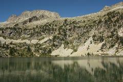 Berglandskap med den reflekterande sjön i spanska Pyrenees royaltyfri bild