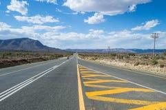 Berglandskap med en Person Crossing huvudvägen Fotografering för Bildbyråer