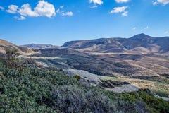 Berglandskap med en väg över berget Arkivfoto