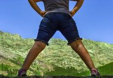 Berglandskap mellan två ben av kvinna arkivfoto