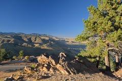 Berglandskap på skymning med den avlägsna staden Arkivfoton