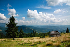 Berglandskap, trähus på en lutning, på himmel Royaltyfria Bilder