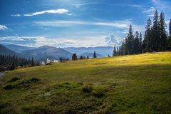 Berglandskappanorama, skönhet av naturtapeten med blå himmel och grönt gräs Arkivbilder