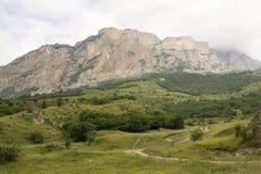 Berglandsväg i utlöparen som döljer i molnen, Kaukasus Ryssland Arkivfoto