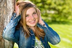 Überglückliches Mädchen außerhalb des Lehnens zum Baum Lizenzfreie Stockbilder