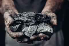 Bergmann hält Kohle, Palmenbeschaffenheit Gewinnendes Konzept, schwarzer Stein stockfotografie