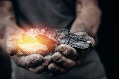 Bergmann hält Kohle, Palmenbeschaffenheit Gewinnendes Konzept, schwarzer Stein lizenzfreies stockfoto