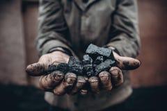 Bergmann hält Kohle, Palmenbeschaffenheit Gewinnendes Konzept, schwarzer Stein lizenzfreie stockfotografie