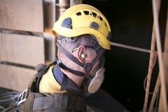 Bergmannarbeitskraft, die einen Ohrenpfropfengeräusch-Sicherheitsschutz beim Arbeiten nahe Lebensdauerbetriebsmaschinerie trägt lizenzfreie stockfotografie
