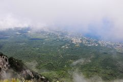 Bergmaxima av Crimean berg som t?ckas med mist p? en bakgrund av bl? himmel och havet arkivbilder