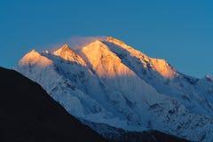 Bergmaximum med första solljus under soluppgång överst i morgonen Rakaposhi bergmaximum i Pakistan royaltyfria bilder