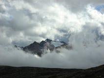 Bergmaximum som kikar till och med molnen Arkivfoto