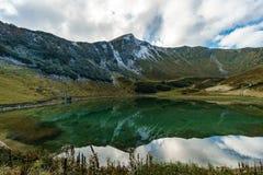 Bergmeer met bezinning van de hemel en de wolken stock afbeelding