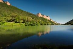 Bergmeer tussen de rotsen en het groene hout Stock Foto's