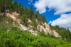 bergmeningen met bomen op achtergrond van blauwe hemel met wolken Royalty-vrije Stock Afbeelding