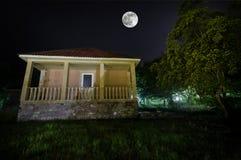 Bergnattlandskap av byggnad på skogen i dimmig natt med månen Grön äng, stora träd och övergett hus på natten Nig Royaltyfri Foto