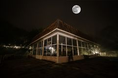Bergnattlandskap av byggnad på skogen i dimmig natt med månen Grön äng, stora träd och övergett hus på natten Nig Arkivfoto