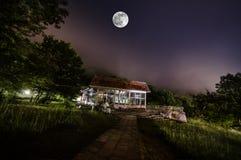 Bergnattlandskap av byggnad på skogen i dimmig natt med månen Grön äng, stora träd och övergett hus på natten Nig Royaltyfria Foton