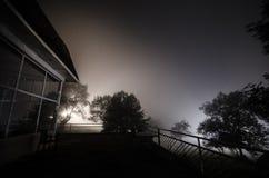 Bergnattlandskap av byggnad på skogen i dimmig natt med månen Grön äng, stora träd och övergett hus på natten Nig Royaltyfri Bild