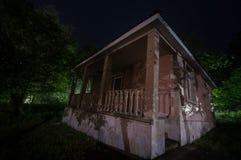 Bergnattlandskap av byggnad på skogen i dimmig natt med månen Grön äng, stora träd och övergett hus på natten Nig Arkivbild