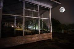 Bergnattlandskap av byggnad på skogen i dimmig natt med månen Grön äng, stora träd och övergett hus på natten Nig Arkivbilder