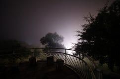 Bergnattlandskap av byggnad på skogen i dimmig natt med månen Grön äng, stora träd och övergett hus på natten Nig Fotografering för Bildbyråer
