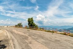Bergopwaartse asfaltweg met bewolkte blauwe hemel met bergen op de achtergrond royalty-vrije stock foto