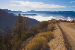 Bergpas, waarvan de wolken over de vallei kunnen worden gezien Royalty-vrije Stock Afbeeldingen