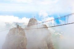 Bergpiek in de wolken met een hangbrug Trap aan hemel stock foto's