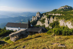 Bergpiek met rotsachtige muren en kerk Stock Foto's