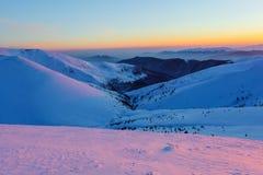 Bergpieken met sneeuw en ijs worden behandeld, waarop dalingen blauwe schaduw, tegen de blauwe hemel die Ijzige dag, schitterende Royalty-vrije Stock Foto's