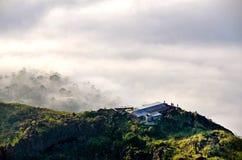 Bergplattelandshuisje boven wolken met een wildernis Stock Foto's
